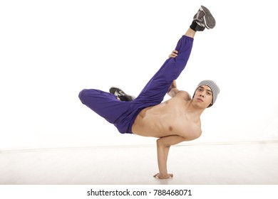 Topless young male dancer sitting on one hand performing breakdance position with legs up, wearing ultraviolet pants. Horizontal image with copyspace, in studio, on white background and wood floor.