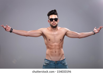 topless young man posing with his arms wide open while looking into the camera. on gray background