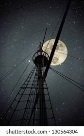 Topmast and cables of an old portuguese ship from the time of the discoveries against a clear full moon night with stars
