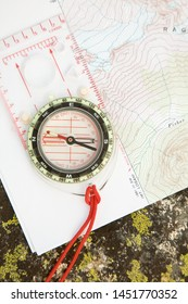 Topographic map and compass on lichen-covered rock. Navigation routefinding in the wilderness. Map is public domain.