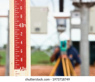 topographic scale with topographer with theodolite back out of focus measuring terrain, distance and unevenness in a construction site
