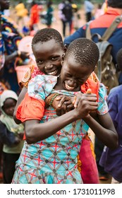 TOPOSA TRIBE, SOUTH SUDAN - MARCH 12, 2020: Teenager from Toposa Tribe smiling and embracing screaming friend from behind while having fun on village square in South Sudan, Africa