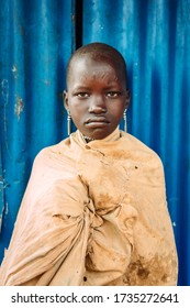 TOPOSA TRIBE, SOUTH SUDAN - MARCH 12, 2020: Teen girl looking at camera while standing against blue building wall in village of Toposa Tribe in South Sudan, Africa