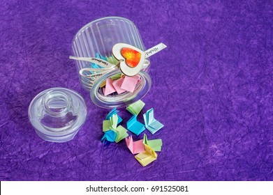 Toppled over glass jar with handmade wooden hearts decorations and ribbon full of colorful folded paper slips.