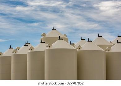 Tops of beige grain bins against contrasty cloudy sky