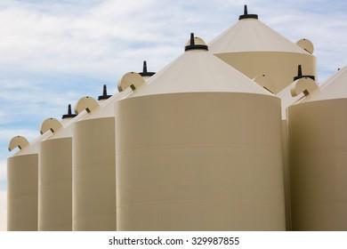 tops of beige grain bins in a diagonal alignment showing filling caps