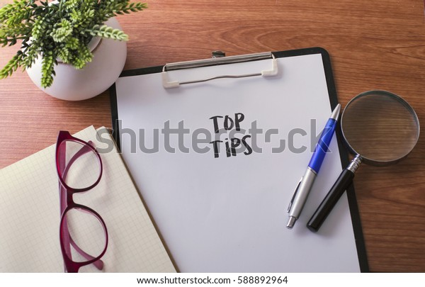 Tops Tips word on paper with glass ballpen and green plant
