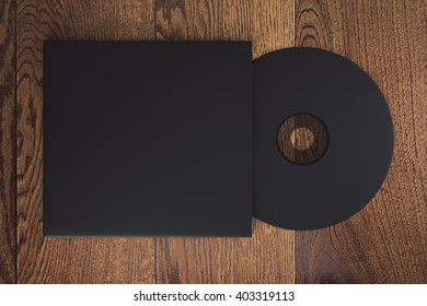 Topview of blank black compact disk with cover on wooden table. Mock up, 3D Rendering
