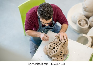 Topview of Ceramist Dressed in an Apron Sculpting Statue from Raw Clay in the Bright Ceramic Workshop.