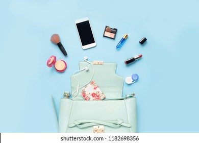 Topview of Fashionable female accessories watch glasses lipstick perfume and blue bag. Overhead of essentials for any girl, on blue background