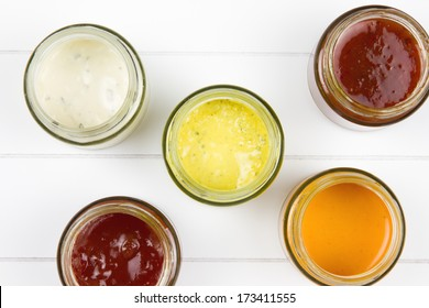 top-view of five jars filled with curry sauce, tomato sauce, garlic sauce, salsa sauce and whiskey sauce on a wooden surface