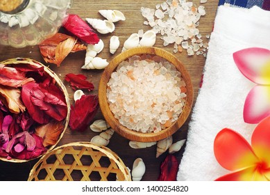 Topview himalaya salt with flowers on towels decorate with dry roses on wood table for scrub spa therapy.