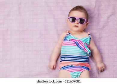 Topview of newborn baby in beachwear on the towel