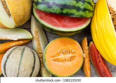topview on a lot of different fresh melons, some are sliced, flat lay