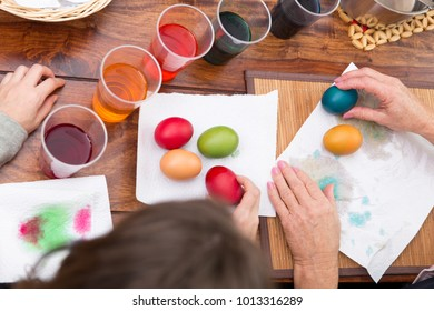 topview on a table with easter eggs and colorful dye, hands of two women