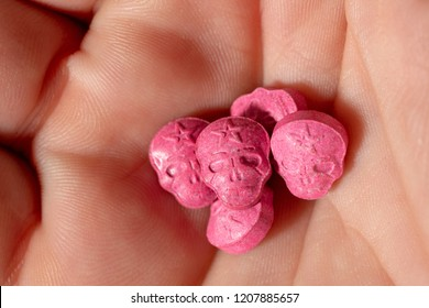 Topview of the palm of a caucasian male hand with a little pile of Red Army Skull, Ecstasy, MDMA or medication pills shaped like a skull.