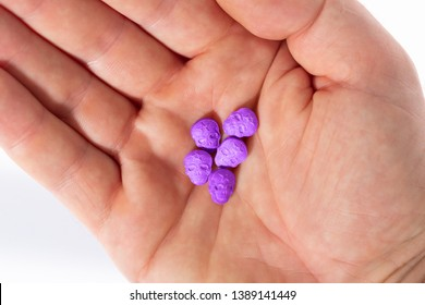 Topview of the palm of a caucasian male hand with a little pile of purple Army Skull, Ecstasy, MDMA, Amphetamine or medication pills shaped like a skull, on a white background.