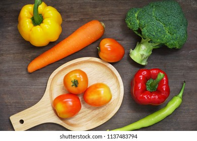 Topview raw vegetables,carrot and tometos and carot and green chilli and bell peper on wood table