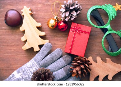 Topview red gift box and glasses and pine cone and christmas tree  and gloves on wood table for christmas party