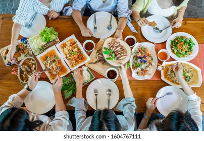 Topview of Thai local food such as Somtum papaya spicy salad, grilled pork, tomyum, vegetable and shrimp curry are arranged on wood table.