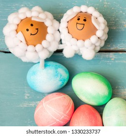 Topview, two lamb shaped figures and dyed easter egg on blue shabby chic background