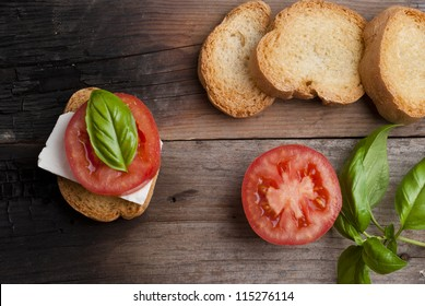 top-view of a wood table with an italian antipasto, with fresh cheese, tomato and basil