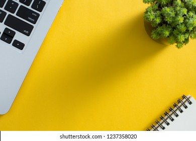 Topview of yellow office desktop with laptop keyboard, green plant and notepad.