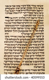 Torah scroll opened to Deuteronomy 6:4, known as the Shema, with a gold yad pointing to the place.