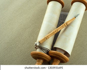 Torah Scrolls on wooden fasteners with a pointer on a rough canvas. Copy space.