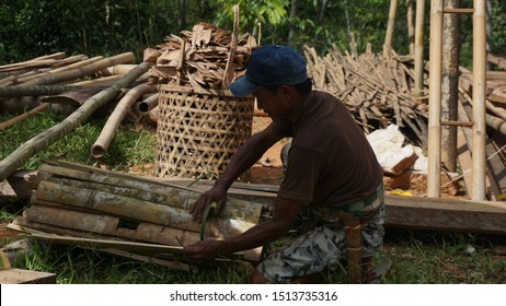 Toraja, Indonesia - December 2019: A middle-aged man is cutting wood and tying wood to make it neat