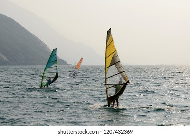 TORBOLE, ITALY - SEPTEMBER 21: as usual  windsurf enthusiasts sail in strong wind on waters of touristic village on Garda lake, shot in bright fall light on sept 21, 2018 at Torbole, Italy