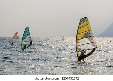 TORBOLE, ITALY - SEPTEMBER 21: as usual  sailbord enthusiasts sail in strong wind on waters of touristic village on Garda lake, shot in bright fall light on sept 21, 2018 at Torbole, Italy