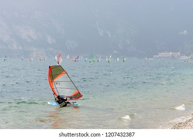 TORBOLE, ITALY - SEPTEMBER 21: as usual winds rallies windsurf enthusiasts in waters of touristic village on Garda lake, shot in bright fall light on sept 21, 2018 at Torbole, Italy
