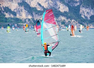 Torbole - Nago, Lago di Garda (Lago Benaco), Italy - July 18, 2019: A windsurfing on Lake Garda in Torbole resort. Windsurfer Surfing The Wind On Waves, Recreational Water Sports, Selective focus