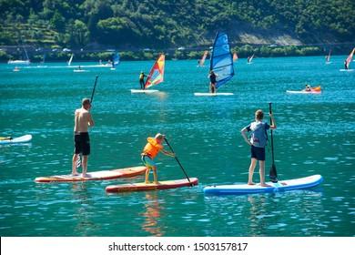 Torbole - Nago, Lago di Garda (Lago Benaco), Italy - July 14, 2019: Warer sports on Lake Garda in Torbole resort. Windsurfer Surfing The Wind On Waves, Recreational Water Sports, Selective focus
