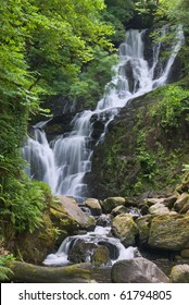 Torc Waterfall, Killarney, Co Kerry, cascades down the mountain side over moss covered rocks amid the trees and bushes of Ireland's native woodland. A long exposure emphasises the flow of the water.