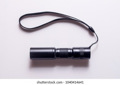 Torch with hand strap isolated on white background. LED aluminium flashlight. Black torch.