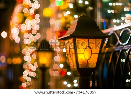 a torch in the street with christmas lights on the window of the restaurant in the