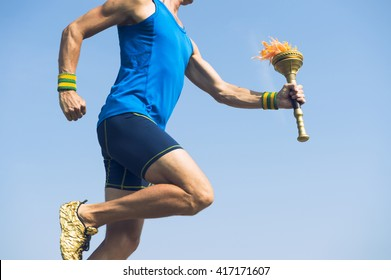Torchbearer athlete in blue running with ceremonial sport torch across sunny blue sky