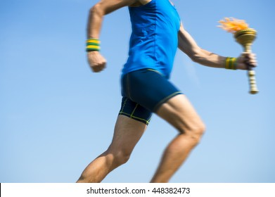 Torchbearer athlete in blue running with sport torch in motion blur across sunny blue sky