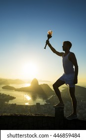 Torchbearer athlete holding sport torch in silhouette against the sunrise skyline with Sugarloaf Mountain in Rio de Janeiro, Brazil