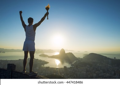 Torchbearer athlete holding sport torch standing in silhouette against the sunrise skyline of Rio de Janeiro, Brazil with Sugarloaf Mountain