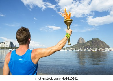 Torchbearer athlete holding sport torch against Rio de Janeiro, Brazil skyline with Sugarloaf Mountain above Guanabara Bay