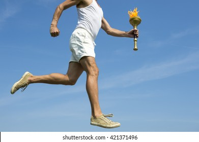 Torchbearer athlete in old fashioned white uniform running with sport torch across sunny blue sky