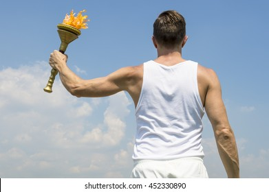 Torchbearer athlete in old fashioned white uniform holding sport torch against sunny blue sky