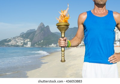 Torchbearer athlete in standing with sport torch in front of Rio de Janeiro Brazil skyline at Ipanema Beach