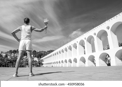 Torchbearer athlete standing with sport torch in front of the Arcos da Lapa Arches in Rio de Janeiro, Brazil