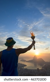 Torchbearer athlete wearing hat holding sport torch standing in silhouette against the sunrise skyline of Rio de Janeiro, Brazil with Sugarloaf Mountain and Guanabara Bay