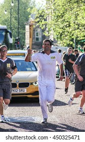 A torchbearer during the olympic torch relay for the London 2012 Olympic Games (London, UK, July 26, 2012)