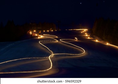 Torchlight draw bright lines over a ski slope during the night procession held by the ski teachers in Folgaria, Italy.